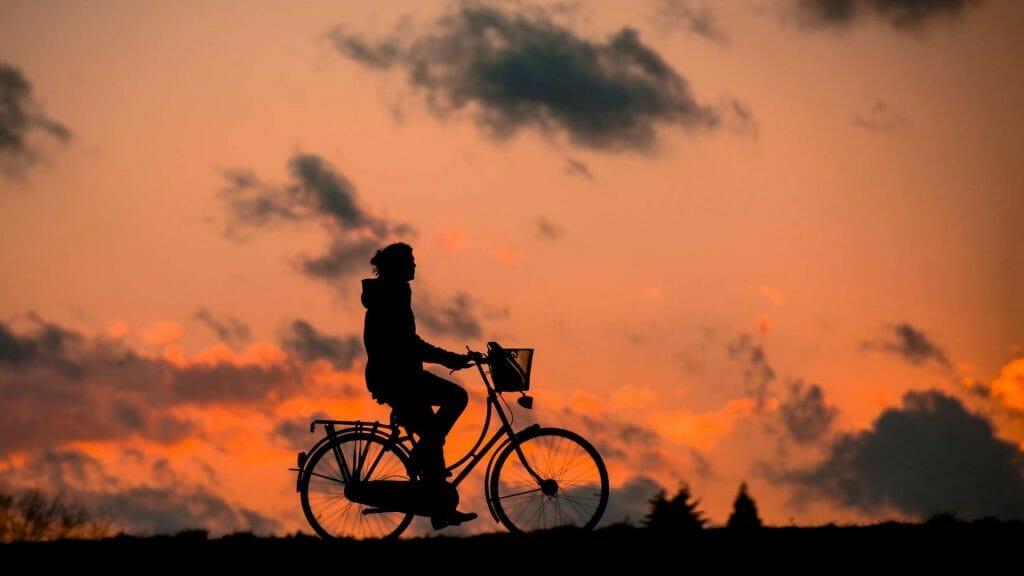 Frau, die in der Dämmerung Rad fährt. / @ pixabay